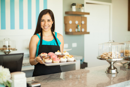 Porträt einer schönen weiblichen Business-Besitzer etwas von ihrem frisch gebackenen Cupcakes zeigt und lächelnd