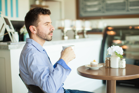 bakery store: Profile view of an attractive young man enjoying a cup of coffee and relaxing in a restaurant