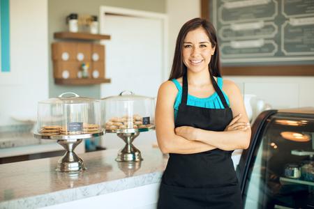 귀여운 히스패닉계 여성 비즈니스 소유자가 그녀의 케이크 가게 앞에 서서 웃는