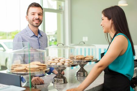 choosing: Portrait of a young good looking man deciding what to get for dessert in a cake shop Stock Photo