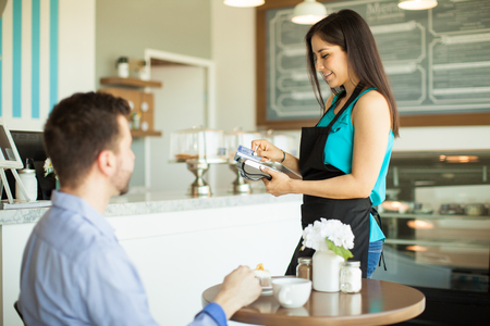 waitress: Beautiful young waitress swiping a credit card from a customer in a bank terminal Stock Photo