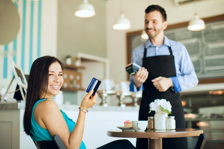 credit card: Retrato de una mujer hispana joven feliz que muestra su tarjeta de crédito después de usarlo en una cafetería