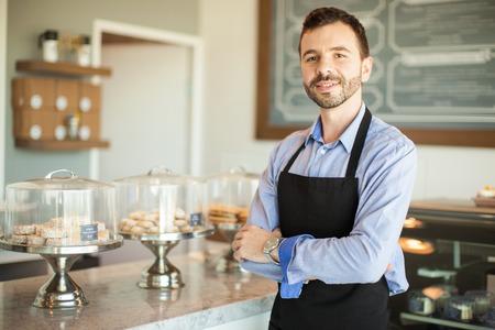 pasteles: Retrato de un empresario joven que llevaba un delantal y de pie frente a su tienda de la torta