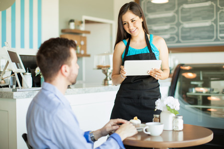 Attraktive junge Kellnerin mit einem Tablet-Computer, einen Auftrag von einem Kunden in einem Café zu nehmen