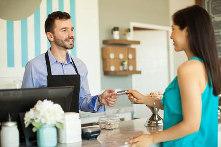 pagando: Morena joven que paga con una tarjeta de crédito en la caja registradora en una tienda de la torta Foto de archivo