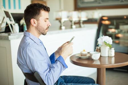 coffee and cake: Profile view of a young man using his smartphone in a cake shop while having a cup of coffee