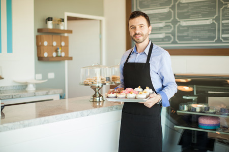 Male business owner in an apron holding a tray of cupcakes and standing in front of his bakery Stock Photo