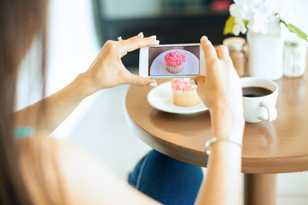 the photo: Point of view of a young woman taking a photo of her food with her smartphone. Picture of food on screen. Stock Photo