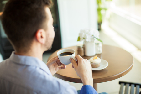 coffee and cake: Point of view of a young man enjoying a cup of coffee by himself in a cafe