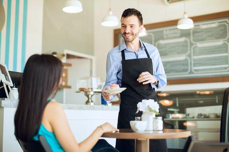 camarero: Retrato de un joven camarero guapo servir un poco de caf� y una magdalena a una clienta en un caf�