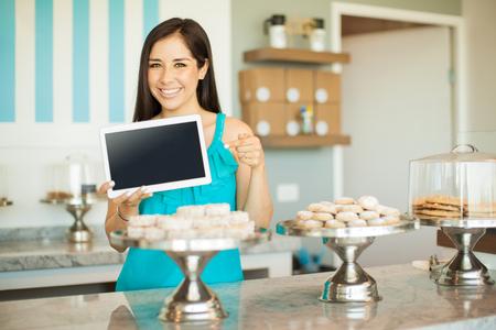Portret van een mooie jonge vrouw met een tablet-computer en wijst op het terwijl je in een banketbakkerij Stockfoto