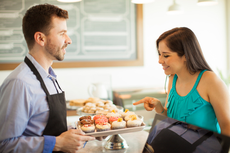 craving: Profile view of a cute female customer pointing at a cupcake she wants to buy in a cake shop. Focus on woman