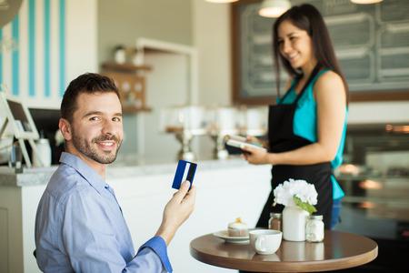 Hombre hispánico joven hermoso que sostiene una tarjeta de crédito después de pagar por su café y una magdalena en un café y sonriendo
