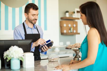 Empleado de sexo masculino en una pastelería deslizar una tarjeta de crédito en una terminal bancaria en la caja registradora en frente de un cliente