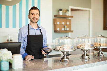 credit card: Hombre latino joven atractiva que sostiene una terminal bancaria junto a una caja registradora en una panadería Foto de archivo
