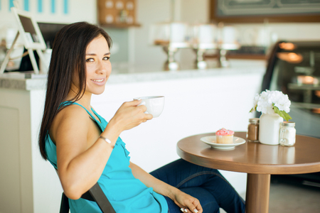 bakery store: Gorgeous young Hispanic woman enjoying a cup of coffee and eating a cupcake in a cake shop Stock Photo