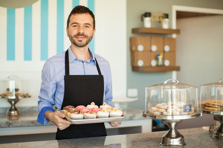 Handsome young man showing a tray of cupcakes from his own cake shop