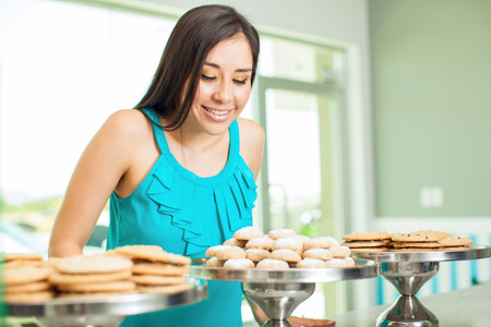 deciding: Beautiful young woman deciding what cookies to get for dessert in a coffee shop Stock Photo