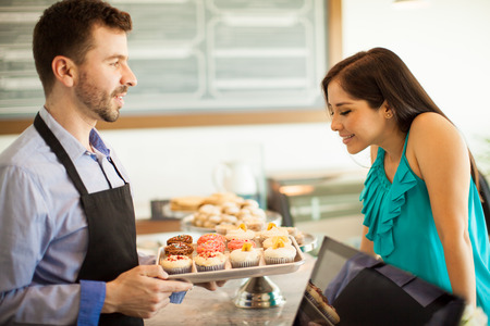 woman shop: Profile view of a young man showing freshly baked cupcakes to a customer across the counter in a cake shop. Focus on woman Stock Photo