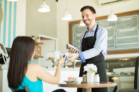 waiter: Young Hispanic waiter taking a credit card from a customer in a coffee shop