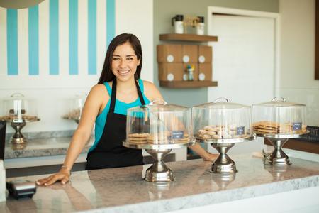かわいい若いヒスパニック系女性彼女のケーキ店でカウンターに立っていると笑みを浮かべて 写真素材