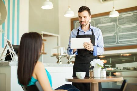 コーヒー ショップでタブレット コンピューターを使用して、顧客の注文を取ってハンサムな若いウェイター