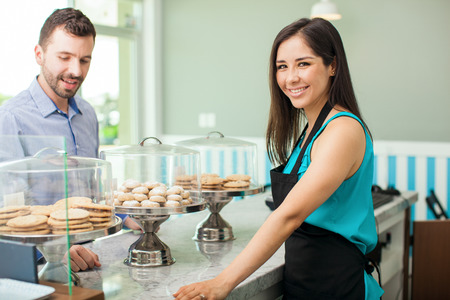 bakery products: Happy young woman showing different types of cookies and pastries to a customer in a bakery Stock Photo