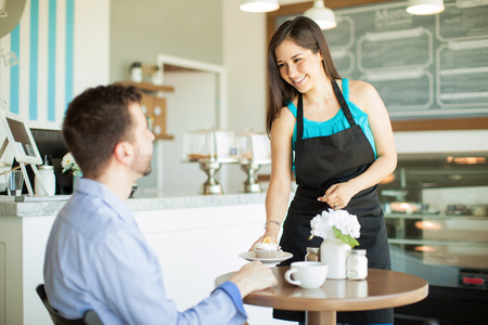 servings: Gorgeous young Latin waitress bringing a cupcake and some coffee to a customer in a cafe Stock Photo