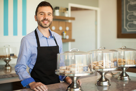 bakery store: Attractive young man standing in front of a the store counter and greeting customers at his bakery