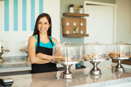 Portrait of a pretty young brunette in an apron selling cookies and pastries in a cake shop
