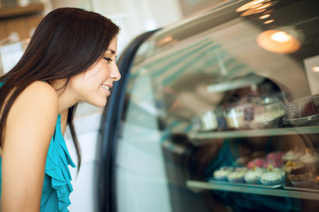 bakery store: Profile view of a gorgeous young brunette deciding what cupcake to buy and standing in front of a fridge