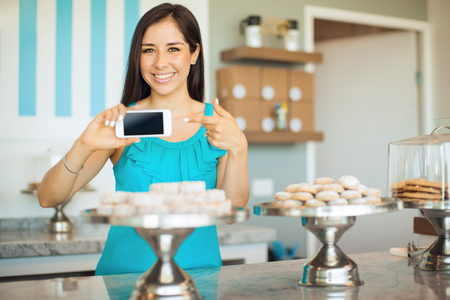 lady on phone: Pretty Hispanic young woman pointing at her smartphone screen and smiling in a bakery