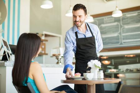 Camarero joven cómoda que sirve una magdalena y un poco de café a uno de sus clientes en una pastelería Foto de archivo