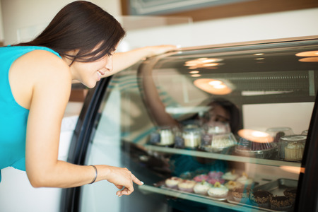 Cute young woman buying some pastries in a cake shop and pointing to them on a refrigerator