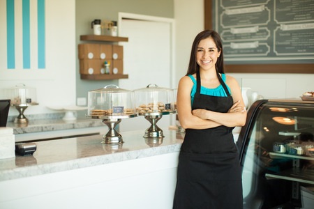 Portrait of a beautiful young business owner standing in front of her bakery and smiling Standard-Bild