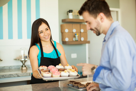 Gorgeous young brunette offering some cupcakes to a customer in a cake shop and smiling