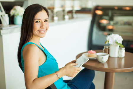 thirties: Pretty Hispanic young woman relaxing and reading on a tablet computer at a coffee shop