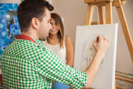 female model: Rear view of a young male artist working on a portrait of a pretty female model in his studio Stock Photo