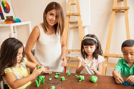 maestra preescolar: Retrato de una hermosa profesor de latín y sus estudiantes trabajan con arcilla durante la clase de escultura Foto de archivo