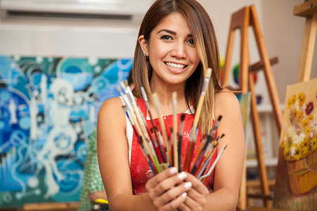 Portrait of a pretty female artist holding a bunch of paintbrushes and smiling while working in her studio