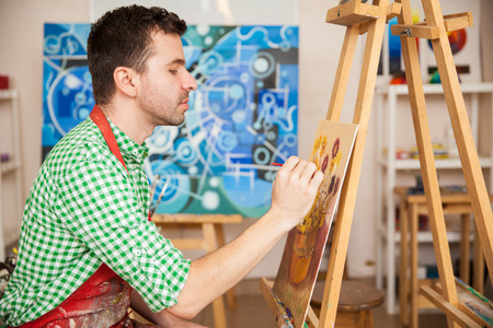 artist: Profile view of a good looking young artist enjoying his work as an artist and working on a painting in his studio Stock Photo