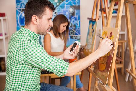peinture: vue de profil d'un jeune homme d'obtenir quelques idées de son smartphone à mettre dans sa peinture dans une école d'art