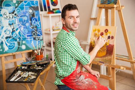 Portret van een jonge aantrekkelijke man die op een schilderij van bloemen en genieten van zijn werk als kunstenaar