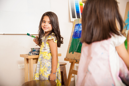 hispanic girl: Beautiful Hispanic little girl holding a brush and smiling during art class at school