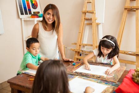 아름다운 라틴 아메리카 미술 교사의 초상화와 그녀의 학생들이 수업 시간에 그리기 재미