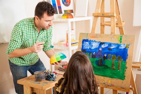 maestra preescolar: Joven y guapo profesor de arte de hablar de colores con una niña durante la clase