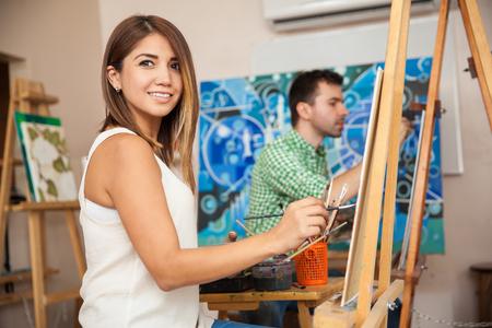 Portret van een mooie jonge vrouw die op een schilderij in een kunstacademie