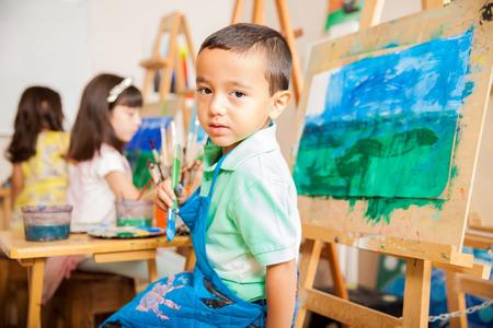 Portrait eines netten kleinen lateinischen Junge trägt eine Schürze und eine Bürste, Malerei eine Landschaft für Kunst-Klasse halten