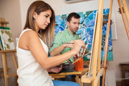 Vista de perfil de una pareja de adultos que trabajan en una pintura en una escuela de arte Foto de archivo