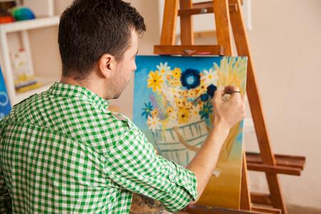 hombre pintando: Vista trasera de un pintor de sexo masculino joven que trabaja en un proyecto en su taller